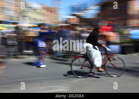 El Alto in Bolivia. Xii oct, 2013. Un concorrente passa di spettatori come lei prende parte a una bicicletta Cholitas gara per gli indigeni Aymara donne. La gara si terrà ad una altitudine di poco più di 4.000 m lungo le strade principali della città di El Alto (sopra la capitale La Paz) per boliviano Giornata della donna che era ieri Venerdì 11 ottobre. Credito: James Brunker / Alamy Live News