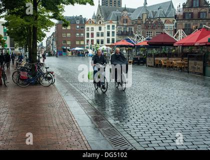 Due uomini in raingear in bici sotto la pioggia Foto Stock