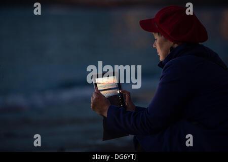 Aberystwyth Wales UK, 15 Ottobre 2013 Una donna con il suo tablet pc per fotografare la drammatica del cielo al crepuscolo su Cardigan Bay, fuori dalla spiaggia a Aberystwyth Wales UK. Dopo un caldo secco e molto soleggiata giornata nel Galles occidentale , le previsioni per i prossimi a causa è per aumentare il cloud e docce di pioggia Photo credit: keith morris/Alamy Live News