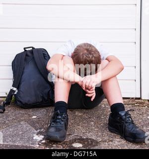 Un ragazzo di 10 guardando triste e depresso nella sua uniforme scolastica che mostra gli effetti di bullismo nel Foto Stock