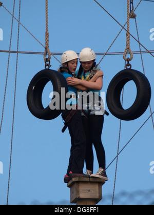 Due ragazze adolescenti permanente sulla parte superiore di un montante cercando spaventata, parte di un avventura Foto Stock