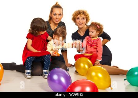 2b59dd3a9017 ... Due madri con i loro bambini a parte con palloncini seduto sul  pavimento insieme Foto Stock