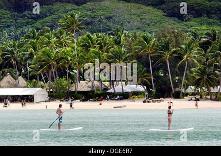 Uomo e donna stand up paddle imbarco su Muri Lagoon a Rarotonga Isole Cook Foto Stock