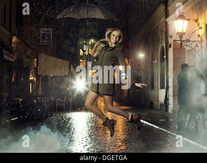 Fantastiche foto di attraente dama jumping in heavy rain Foto Stock