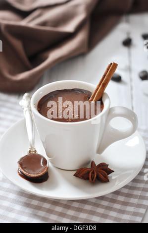 Cioccolata in tazza con polvere di cacao e cannella stick su sfondo di legno Foto Stock