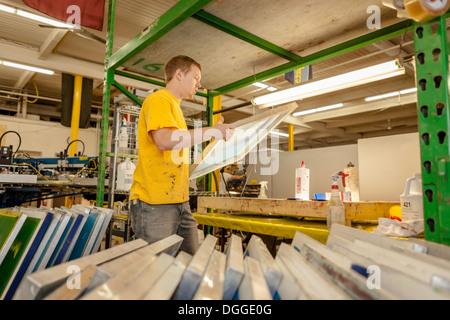 Lavoratore del telaio portante nella stampa serigrafica workshop Foto Stock