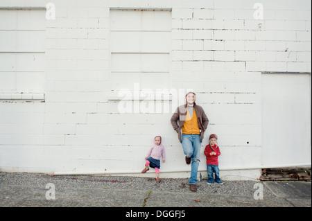 Metà uomo adulto e il figlio e la figlia appoggiata contro la parete, ritratto