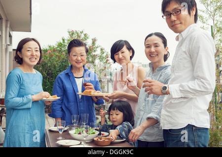Tre generazioni la famiglia di mangiare all'aperto, ritratto Foto Stock