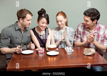 Quattro amici festeggia il compleanno in ristorante Foto Stock