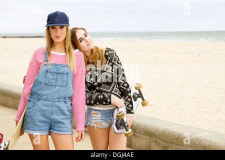 Due giovani donne azienda skateboard a beach Foto Stock