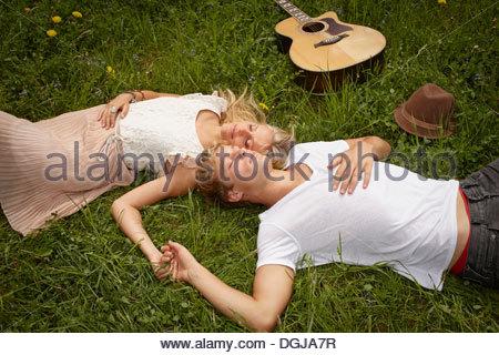 Coppia giovane sdraiato sul prato con gli occhi chiusi Foto Stock