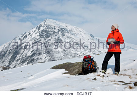 Considerato l uomo in piedi di fronte a monte  Scalatore femmina con mappa  sulla coperta di neve montagna 4764580019b
