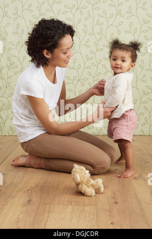 Azienda madre bambina prendendo i primi passi Foto Stock