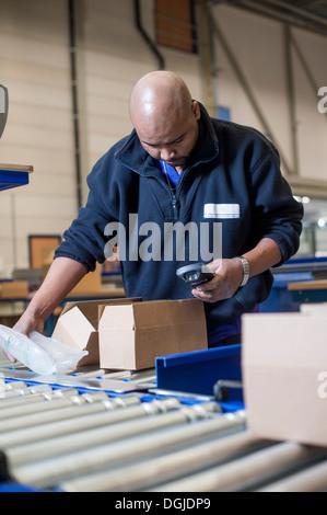 Magazzino maschio lavoratore controllo scanner di codici a barre Foto Stock