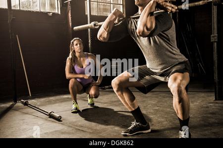 Giovane uomo e personal trainer lavora in palestra Foto Stock