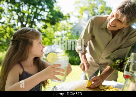 Nella fattoria. Bambini e adulti che lavorano insieme. Una ragazza e un uomo adulto facendo una limonata. Il taglio Foto Stock