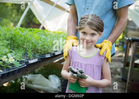 In azienda i figli adulti che lavorano insieme uomo giovane bambino guanti da giardinaggio in piedi accanto al banco Foto Stock