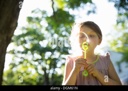 All'aperto in estate. Una giovane ragazza a soffiare bolle in aria sotto i rami di un grande albero. Foto Stock