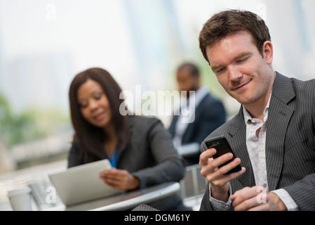 L'estate. Tre persone sedute al di fuori del lavoro. Utilizzando una tavoletta digitale e i telefoni intelligenti. Foto Stock