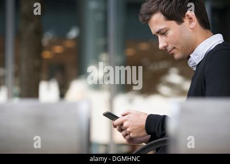 Estate in città. Un uomo seduto su un banco utilizzando un telefono intelligente. Foto Stock