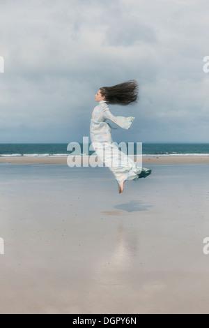 Una ragazza in un abito floreale è il salto sulla spiaggia Foto Stock