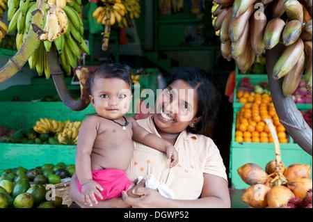 Fornitore femmina mentre tiene il suo bambino, stallo del mercato per la vendita di frutta e verdura, Bentota, Aluthgama, Sri Lanka