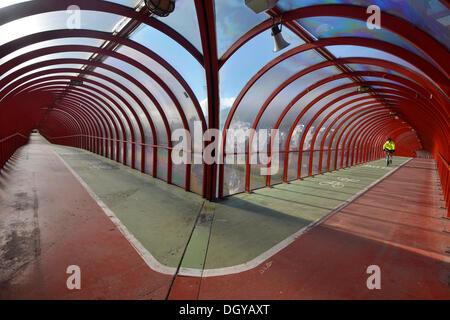 Il ciclista è a cavallo su un ponte pedonale coperto e ponte di bicicletta, Glasgow, Scotland, Regno Unito Foto Stock