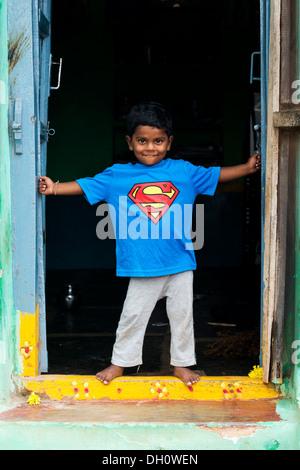 Giovane ragazzo indiano indossando un superman t shirt in piedi la porta della sua casa in un territorio rurale villaggio indiano. Andhra Pradesh, India