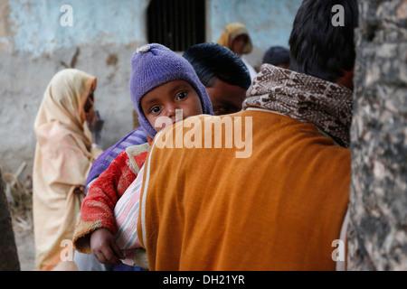 Un giovane bambino sul braccio di suo padre, gli abitanti di un villaggio vicino Rajbiraj, Terai regione, Nepal, Foto Stock