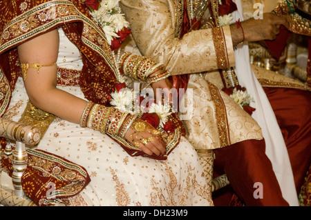Sposa e lo Sposo vestito in tutte le loro raffinatezze che festeggiano il loro tradizionale matrimonio induista. Foto Stock