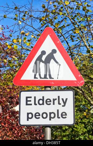 Segno di traffico avvertimento che gli anziani forse cercando di attraversare la strada. Foto Stock