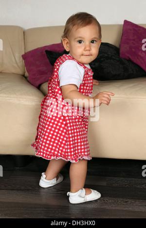Una piccola bambina cerca di camminare, sta compiendo i suoi primi passi Foto Stock