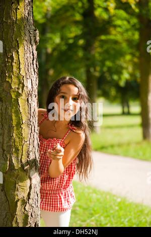 Ragazza sorridente guardando fuori da dietro un albero Foto Stock
