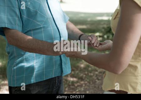 Una donna e un uomo anziano che fissano ciascuna altre mani