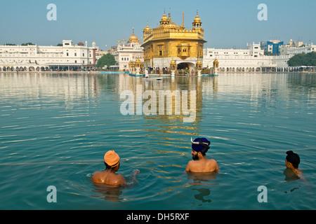 Tempio d'oro, Hari Mandir, il principale santuario della religione sikh, tre pellegrini indossa turbanti di prendere Foto Stock