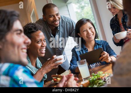 Un gruppo di persone che si incontrano in un bar. Utilizzando le compresse di digitale e i telefoni intelligenti. Foto Stock