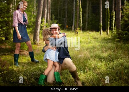 Un uomo che abbraccia un bambino. Una famiglia in un bosco a piedi. Foto Stock
