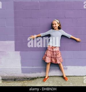 Una ragazza di 10 anni in una gonna a più livelli, in piedi con le braccia aperte, appoggiata contro una parete. Foto Stock