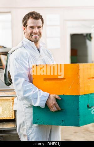 Felice apicoltore maschio che trasportano pila di casse a nido d'ape Foto Stock