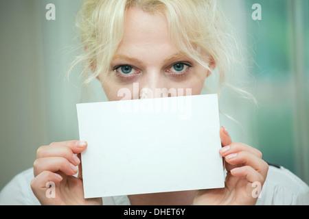 Giovane donna in possesso di una carta vergine oltre il suo volto Foto Stock