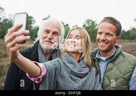 Metà donna adulta prendendo fotografia con la fotocamera del telefono Foto Stock