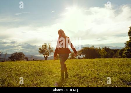 Giovane donna nel campo a piedi Foto Stock
