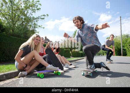Quattro giovani donne seduta sul marciapiede guardando skateboarders Foto Stock