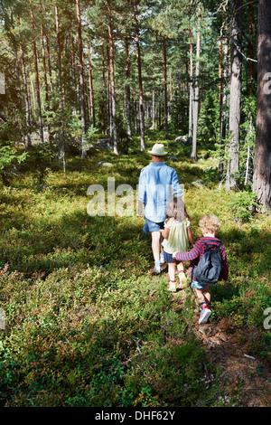 Padre e figlie camminare attraverso la foresta