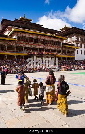 Il Bhutan, Thimpu Dzong, Tsechu annuale, le donne e i bambini di entrare festival Ground Foto Stock