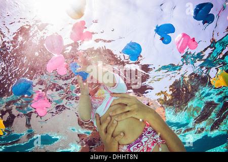 Baby girl per raggiungere le papere di gomma in acqua, l'angolo basso Foto Stock