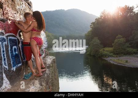 Coppia giovane la condivisione di un bacio sulla sporgenza di roccia, Amburgo, Pennsylvania, STATI UNITI D'AMERICA Foto Stock