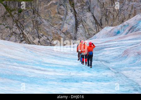 Quattro persone che camminano su Mendenhall Glacier, Alaska, STATI UNITI D'AMERICA Foto Stock