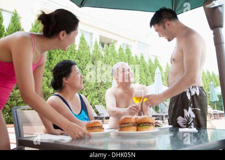 Famiglia sorridente mangiare hamburger dal pool in vacanza Foto Stock