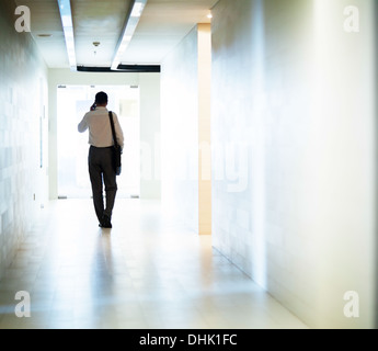 Imprenditore a camminare lungo il corridoio sul telefono Foto Stock